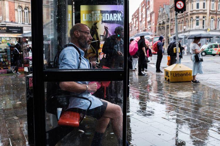 Full length of man sitting on street in city