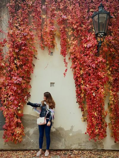 Mid Adult Woman Taking Selfie While Standing By Wall During Autumn