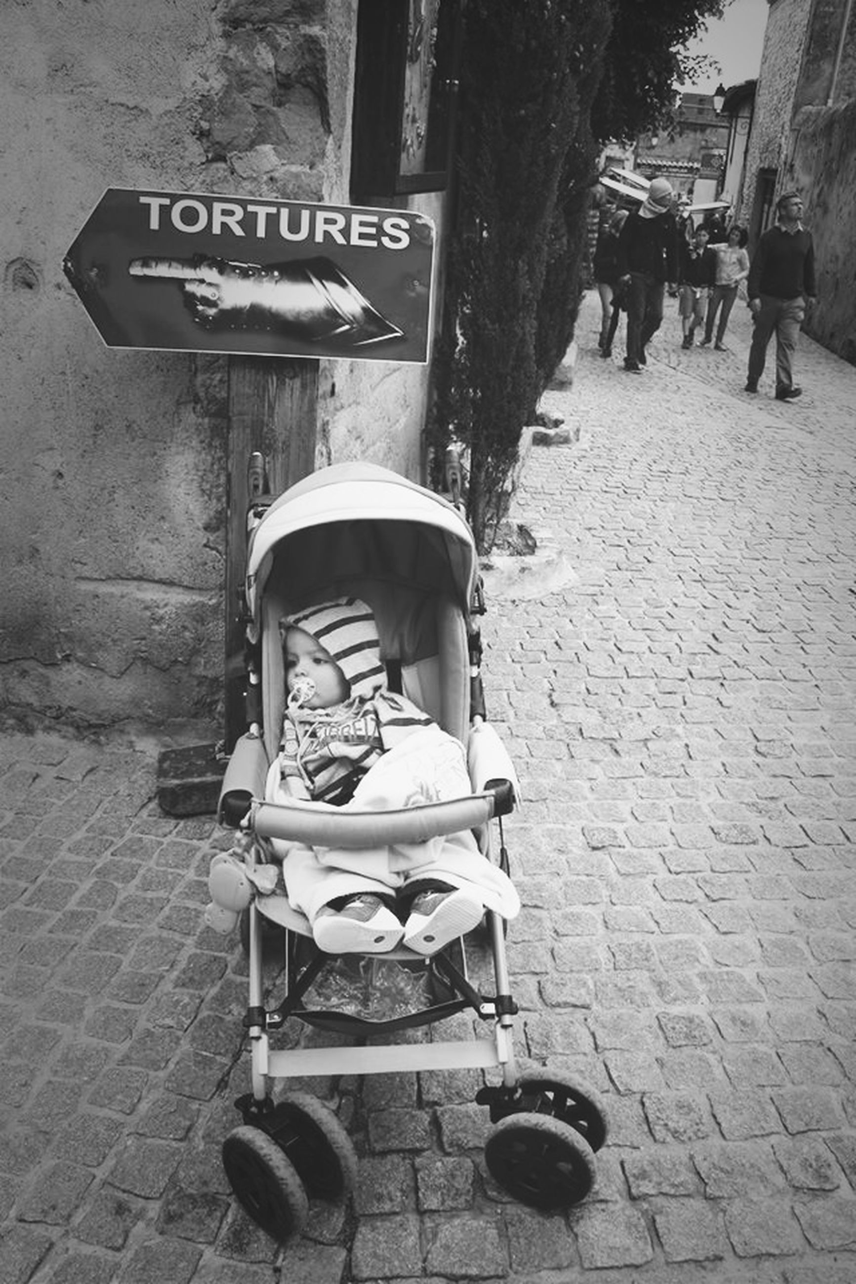 chair, street, cobblestone, text, communication, day, sidewalk, sidewalk cafe, incidental people, building exterior, outdoors, empty, built structure, city, architecture, footpath, absence, western script, cafe, table