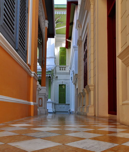 The hallway between old-fashioned buildings, paved with tiles and beautiful patterns. Ceiling Cornices Green Color Hallway Roof Stencil Architecture Balcony Built Structure Columns Corridor Day Door Floor Frame Indoors  Louver No People Orange Color Outlet Pattern Tile Windows