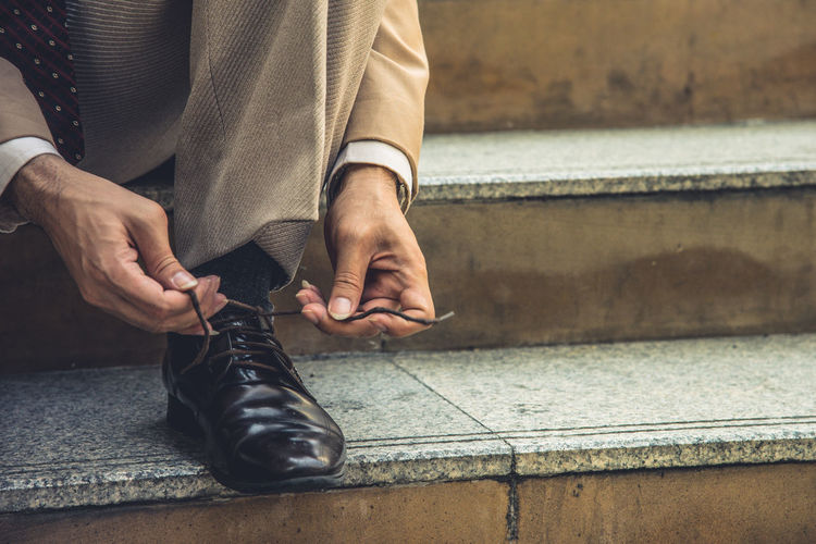 Low section of businessman tying shoelace on steps