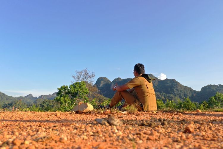 Man sitting on land against clear sky