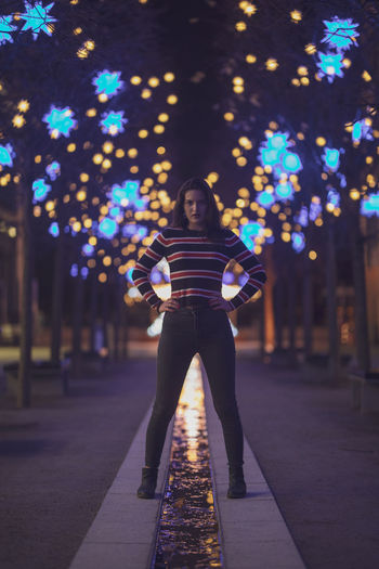 Portrait of woman standing on footpath against illuminated lights at night