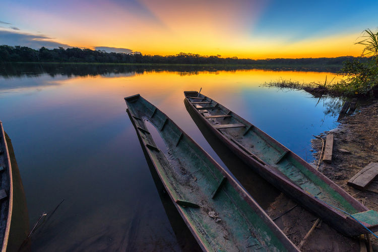 Wooden Canoes Moored On Lake Against Sky During Sunset