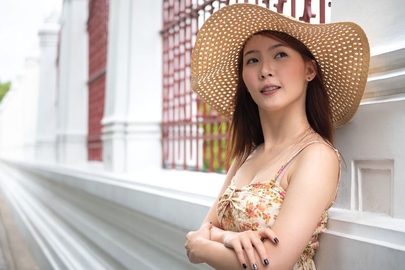 Travel Bangkok concept. Young Asian woman with smiling at Wat arun temple Bangkok Travel Traveling Adult Architecture Beautiful Woman Beauty Clothing Day Front View Hat Leisure Activity Lifestyles One Person Outdoors Portrait Smiling Woman Standing Summer Sun Hat Temple Travel Thailand Women Young Adult Young Women