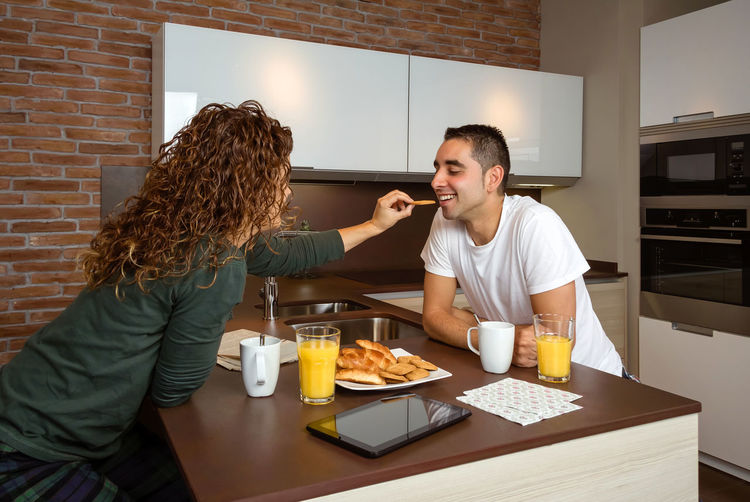 Young couple having fun while having breakfast in the kitchen feeding each other Horizontal Orange Juice  Croissant Enamored Family Girlfriend Relaxing Husband Boyfriend Wife Relationship Lifestyle Love Cup Caucasian Healthy Two Coffee Girl Meal Together Young Woman Kitchen Man Indoors  Food Morning Technology Newspaper Digital Tablet Cheerful Happiness Enjoy Smile Male Home People Female Smiling Playfully Cookies Feeding  Having Fun Couple Happy Breakfast