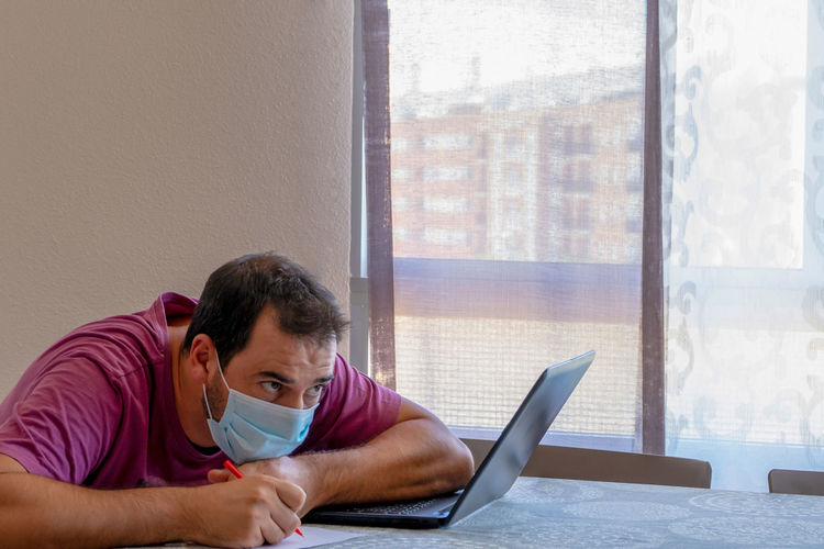 Side view of man wearing flu mask using laptop at home