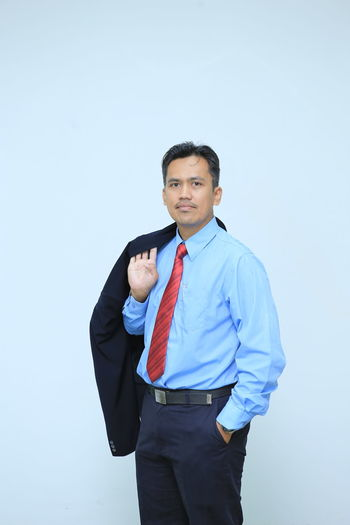Portrait of businessman standing against colored background
