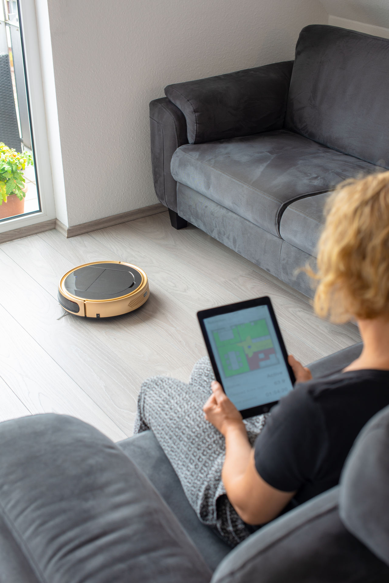 High angle view of woman using digital tablet while sitting on sofa at home