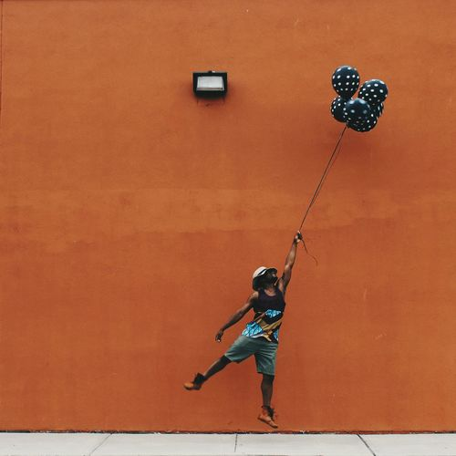 Full length of man with helium balloons flying against wall