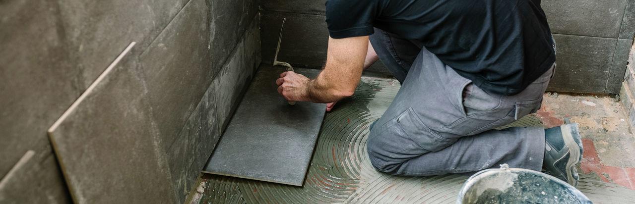 High angle view of mason worker applying tiles