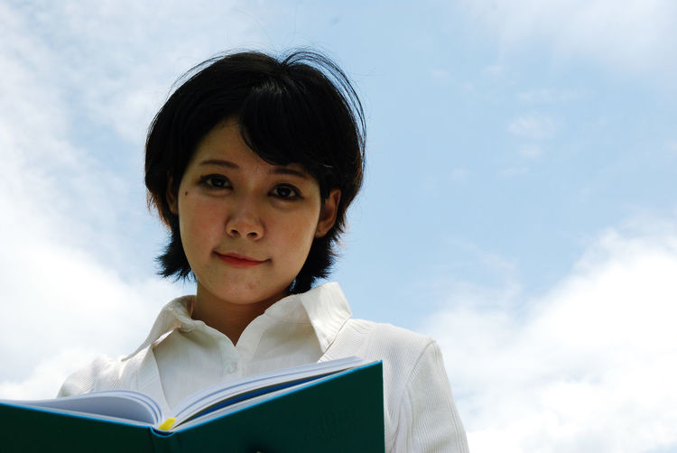 Beautiful woman holding white paper book on sky background. Portrait Book Publication Headshot Sky Education One Person Low Angle View Cloud - Sky Looking At Camera Front View Day Leisure Activity Learning Reading Child Student Activity Nature Outdoors Studying Human Face Pre-adolescent Child Innocence