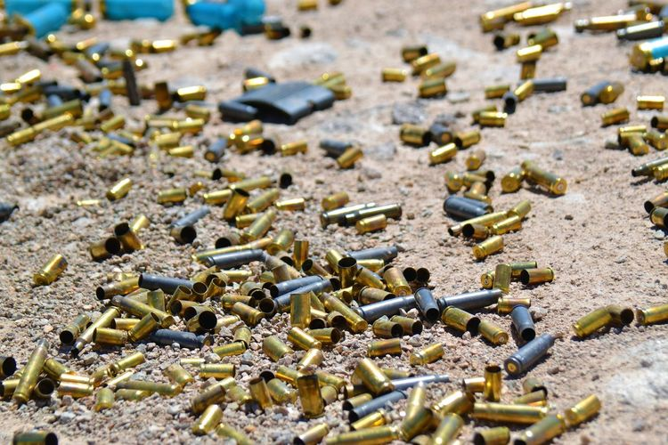 a lot of bullet shells in rocky sand. different type Abundance Barrett 82A1 Bullet Bullets Cartridge Close-up Crime Danger Day Deadly Death Gun Gun Range Large Group Of Objects Murder No People Outdoors Pile Of Bullets Power Selective Focus Shadow Shooting Range  Sniper Violence Weapon