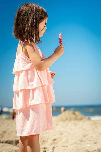 Cute girl looking away while eating ice cream at beach