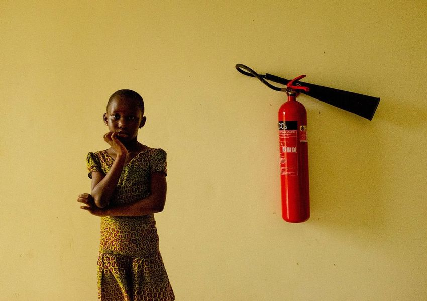 Cape Coast, Ghana Fire Extinguisher Girl Portraiture Portrait Photography Portrait Yellow Cape Coast Ghana Representation Creativity Three Quarter Length Human Representation The Portraitist - 2018 EyeEm Awards The Photojournalist - 2018 EyeEm Awards