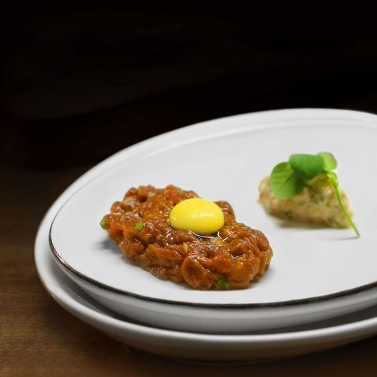 Beef Tartare Amuse Bouche with raw egg Amuse Bouche Beef Black Background Studio Beef Tartare Close-up Day Egg Fine Dining Food Food And Drink Freshness Fried Egg Healthy Eating Indoors  Meat No People Plate Ready-to-eat Studio Shot