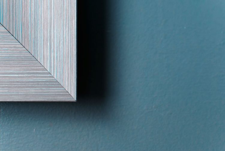 Cropped Image Of Picture Frame Against Blue Wall