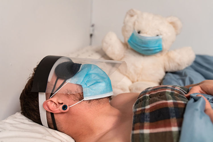Close-up of man wearing face shield sleeping on bed