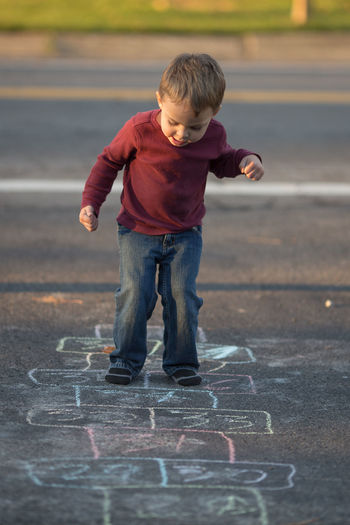 Full length of boy playing hopscotch on road