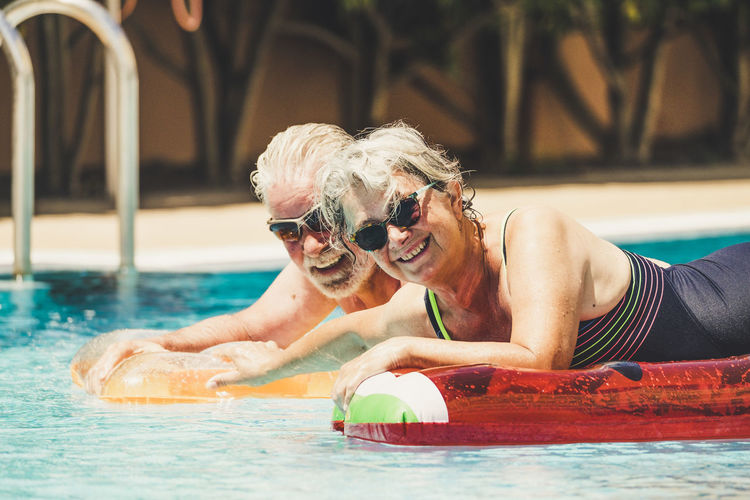 Portrait of smiling senior couple swimming in pool