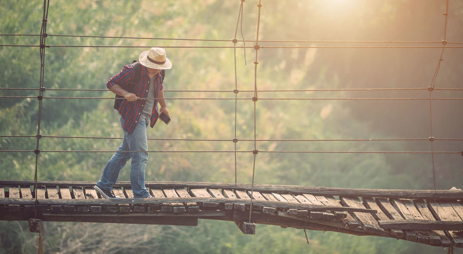Side view of man standing on railing against bridge