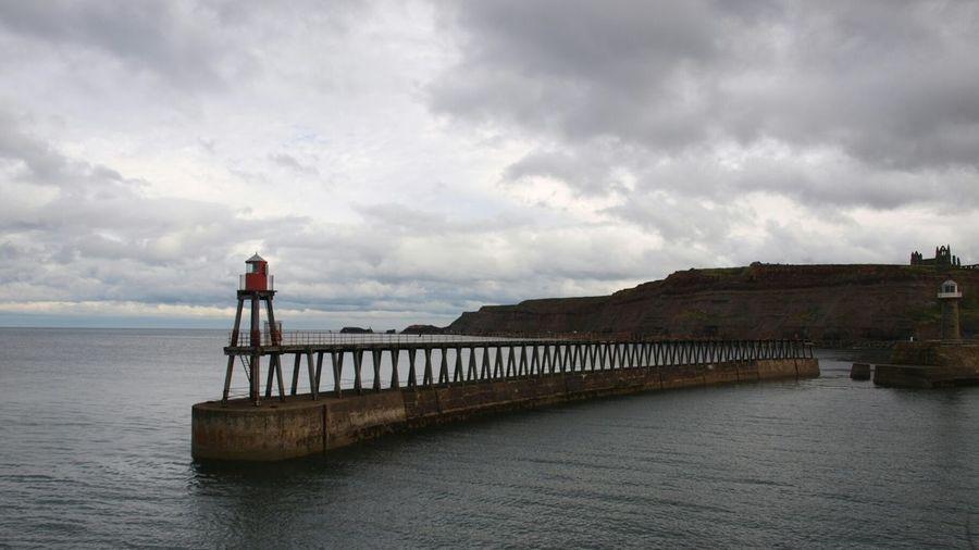 Beacon On Pier In Sea Against Cloudy Sky