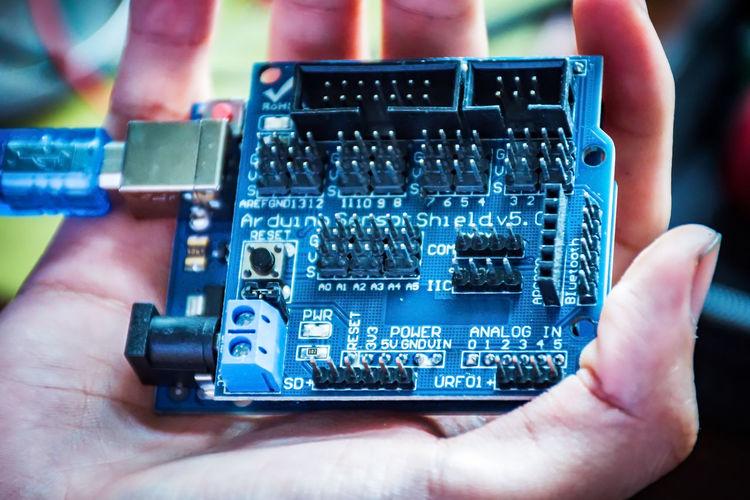 Cropped hand repairing circuit board in workshop
