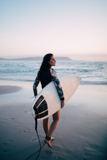 Sea Beach Full Length One Person Land Water Leisure Activity Sky Casual Clothing Young Adult Real People Lifestyles Sunset Nature Scenics - Nature Horizon Side View Holding Horizon Over Water Outdoors Beautiful Woman Surfing