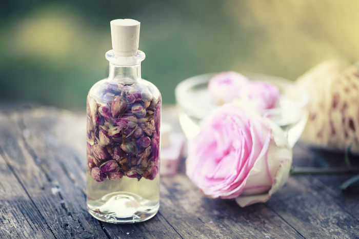 aromatherapy dried roses and massage oil in a glass bottle Aromatherapy Aromatherapy Oil Beauty Beauty Product Bottle Essentialoils Massage Oil Oil Outdoors Pink Color Rose - Flower Scented Wood - Material Wooden Background