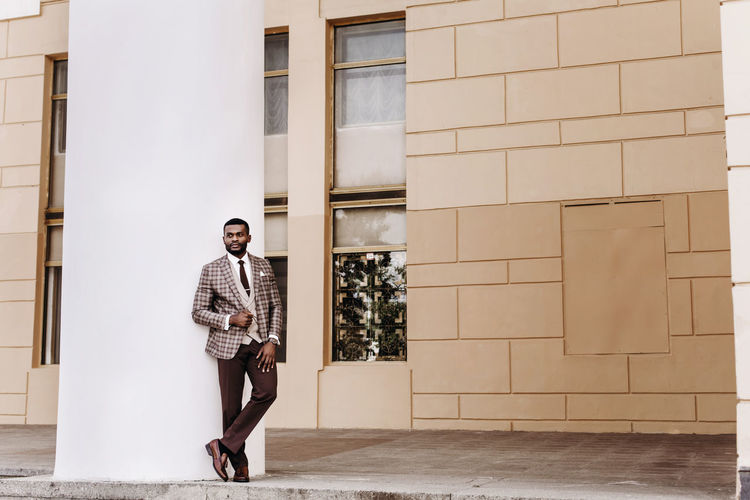 Full length of man wearing suit standing against wall
