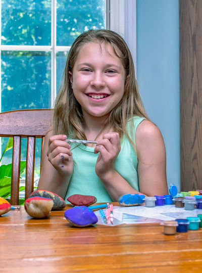 Portrait of smiling girl sitting on table