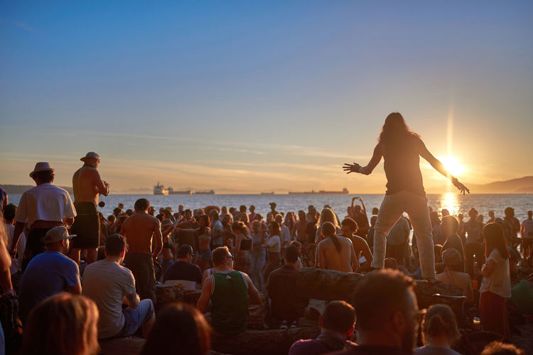 People at music concert against sky during sunset