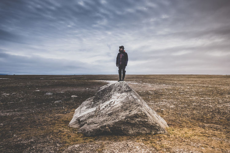 Man Standing On Rock Against Cloudy Sky