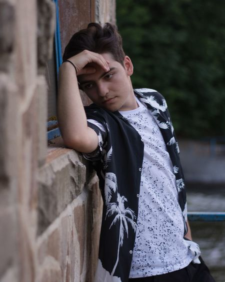 Thoughtful Teenage Boy Leaning On Stone Wall