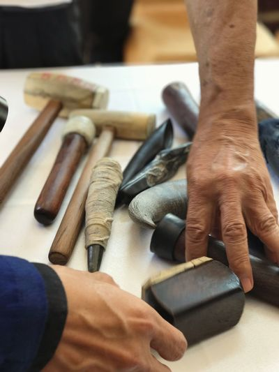 Cropped Image Of Hands Picking Tools On Table