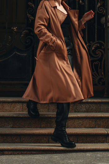 Cropped figure of young woman wearing stylish brown overcoat and black outfit. street casual