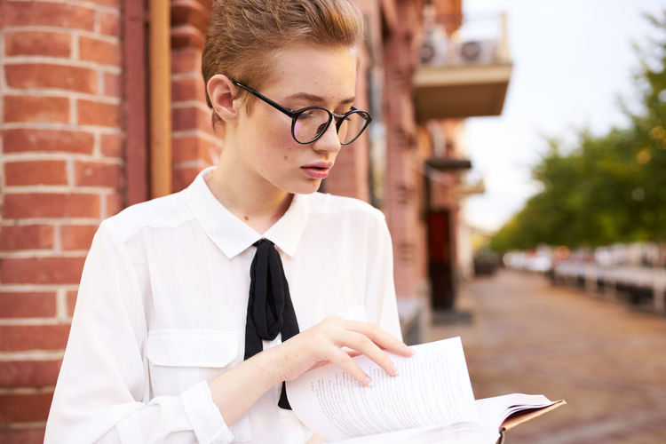 Young woman looking away while holding book