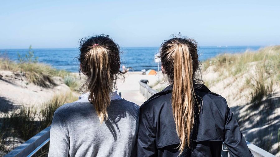 Rear view of female friends at beach against sky