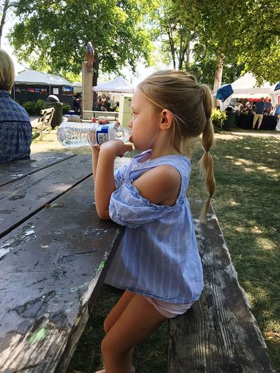 Side View Of Girl Drinking Water From Bottle While Sitting On Bench
