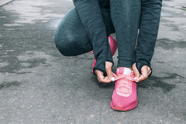 Low Section Of Woman Tying Running Shoes