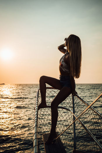 Water Sea One Person Sky Beauty In Nature Leisure Activity Real People Lifestyles Sunset Scenics - Nature Horizon Over Water Horizon Women Young Adult Nature Adult Young Women Nautical Vessel Outdoors Hairstyle Beautiful Woman