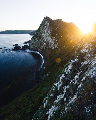 Lighthouse Beauty In Nature Cliff Environment Flowing Water Land Lens Flare Mountain Nature No People Non-urban Scene Outdoors Rock Rock - Object Scenics - Nature Sea Sky Solid Sunlight Sunset Tranquil Scene Tranquility Water