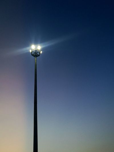Low angle view of illuminated floodlight against blue sky