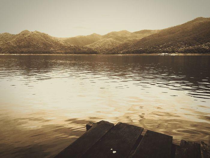 นั่งอยู่ฝั่งนี้ อยากไปฝั่งโน้น Sitting Alone Sitting Outside Lake Water Nature Tranquility Scenics Tranquil Scene Beauty In Nature Reflection Tree No People Mountain Outdoors Rippled Sunset Sky Day