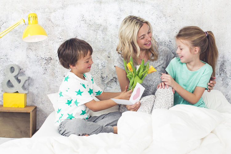 Smiling woman holding greeting card while sitting with children on bed at home