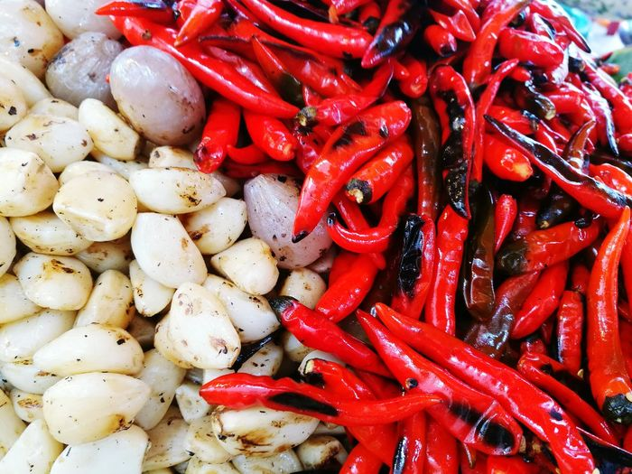 Close-Up Of Fried Red Chili Peppers And Garlic Cloves For Sale