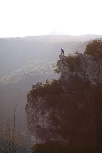 Man on rock against sky
