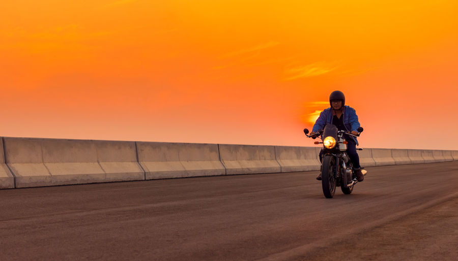 On the route to a summer vacation on a motorcycle, on an asphalt highway, a biker dude wearing .