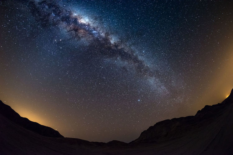 Starry sky and Milky Way arch, with details of its colorful core, outstandingly bright, captured from the Namib desert in Namibia, Africa. The Small Magellanic Cloud on the left hand side. Keywords: milky way,star,night,galaxy,desert,glow,namib,africa,sky,southern hemisphere,camping,south africa,namibia,fisheye,namib naukluft national park,landscape,valley,adventure,kalahari,arc,nature,space,dune,nebula,science,fantasy,dark,star field,exploration,travel,fish-eye,planet,solar system,astronomy,ethereal,physics,constellation,dreams,clear sky,soul searching,remote,perfection,infinity,beauty,universe,celestial,hills,distant,nobody Astronomy Beauty In Nature Constellation Galaxy Landscape Low Angle View Milky Way Mountain Nature Night No People Outdoors Scenics Sky Space Space Exploration Star - Space Star Trail Tranquil Scene Tranquility