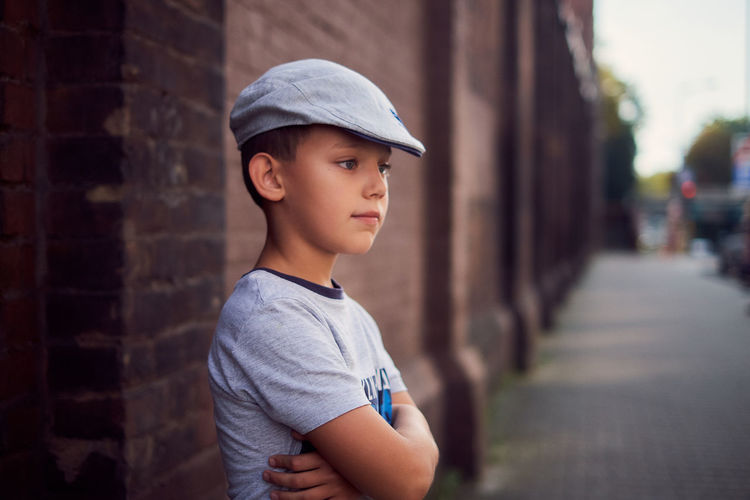 Close-up of cute boy wearing hat standing by building outdoors